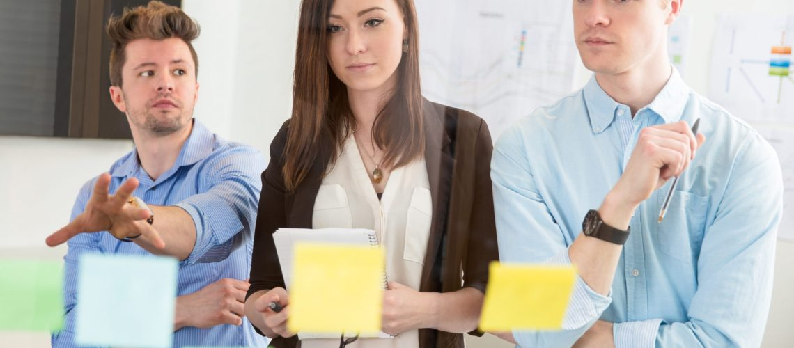 Confident businesswoman looking at strategies on adhesive notes while standing by male colleagues in office